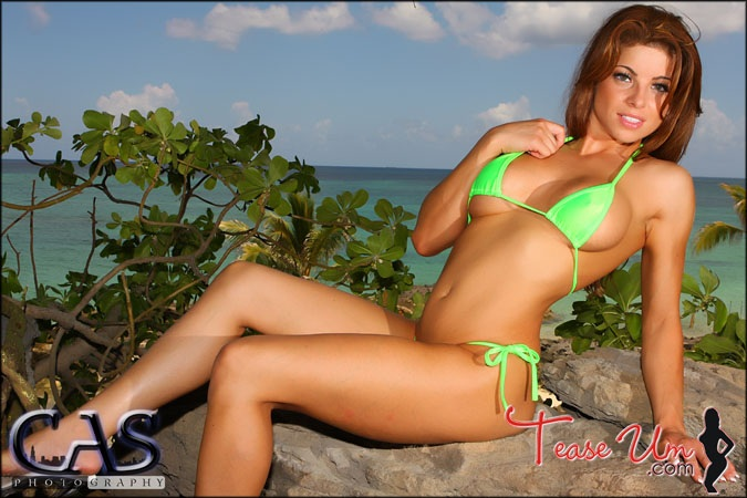 redhead bikini model on rock green